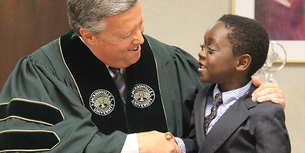 President Cost shakes a student's hand
