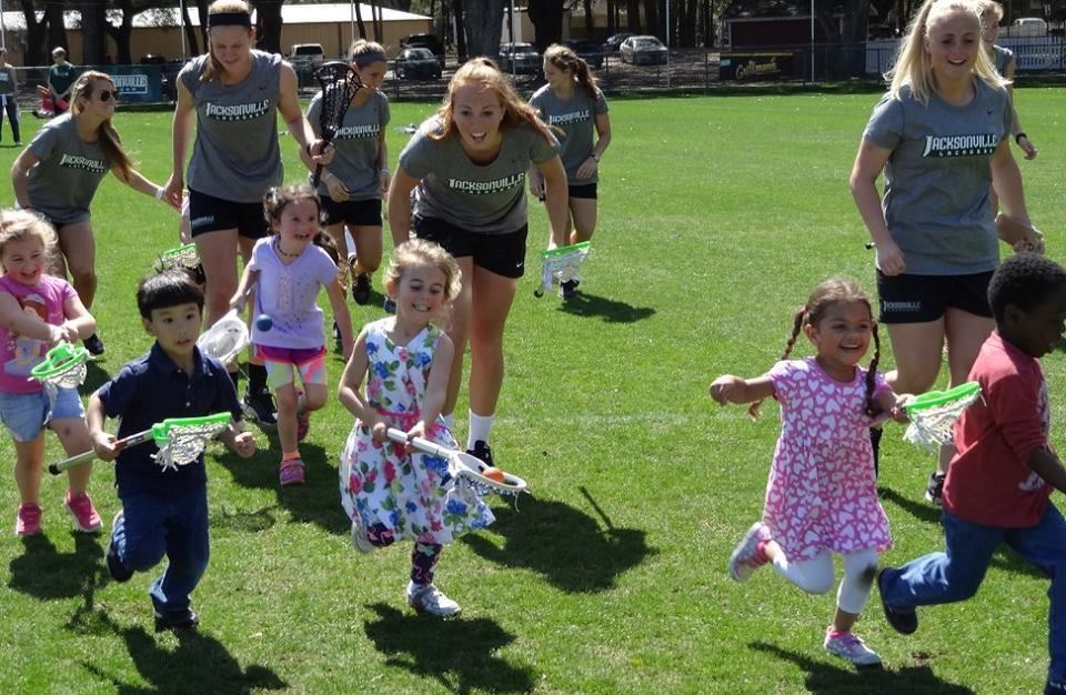 Women's lacrosse team plays with kids